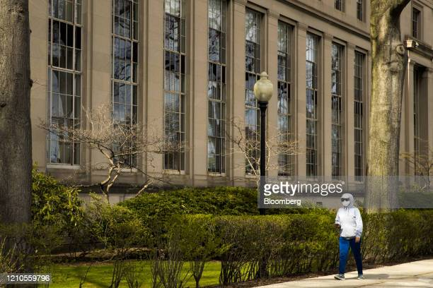 A pedestrian wearing a protective mask walks past on the Massachusetts Institute of Technology campus in Cambridge Massachusetts US on Monday April...