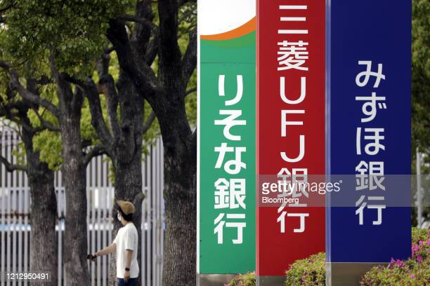 Pedestrian wearing a protective mask walks past signage for Resona Bank Ltd., from left, MUFG Bank Ltd. And Mizuho Bank Ltd. In Tokyo, Japan, on...