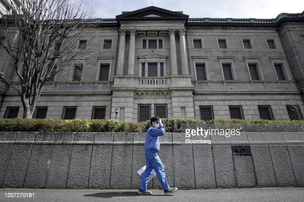 Pedestrian wearing a protective mask walks past the Bank of Japan headquarters in Tokyo, Japan, on Monday, March 16, 2020. The Bank of Japan...