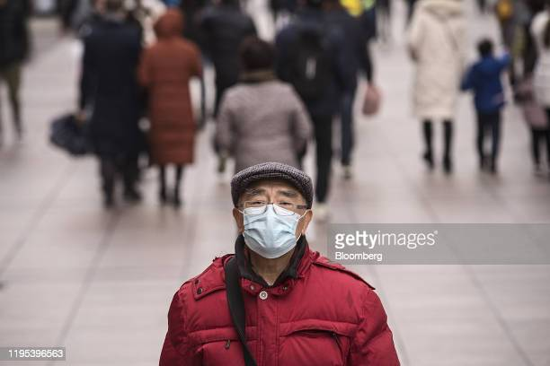 A pedestrian wearing a protective mask walks through the Nanjing East Road shopping area ahead of the Lunar New Year in Shanghai China on Thursday...