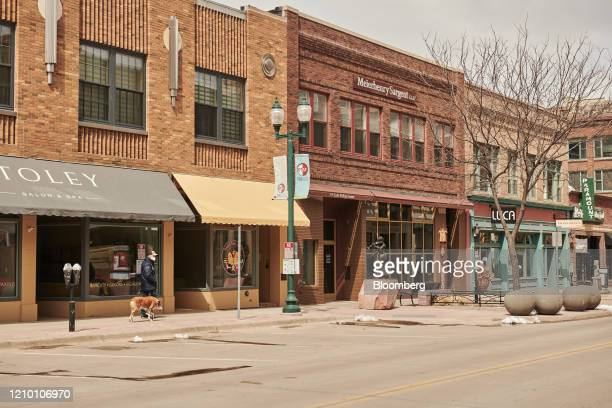 A pedestrian wearing a protective masks walks a dog past closed stores in downtown Sioux Falls South Dakota US on Wednesday April 15 2020 South...
