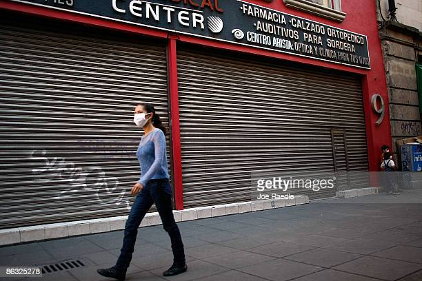 A pedestrian wearing a surgical mask to help prevent contamination with swine flu walks past shuttered business on May 1 2009 in Mexico City Mexico...
