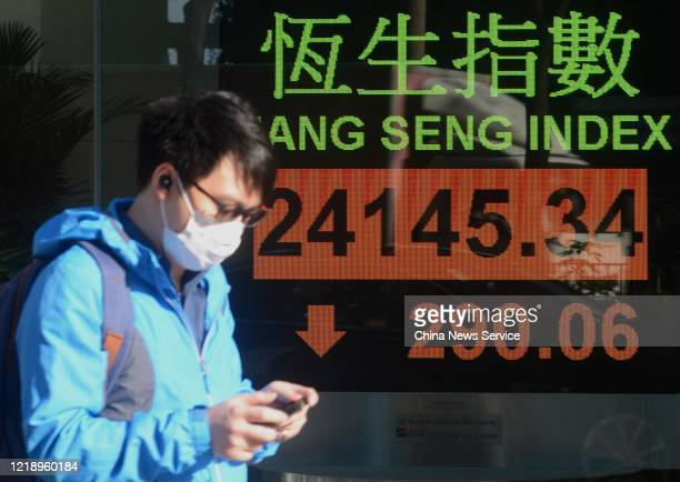A pedestrian wearing face mask walks by an electronic screen displaying the Hang Seng index on April 15 2020 in Hong Kong China