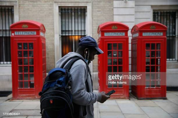 Pedestrian wearing face mask walks past a row of telephone boxes on July 4, 2021 in London, England. Robert Jenrick, British minister for housing...