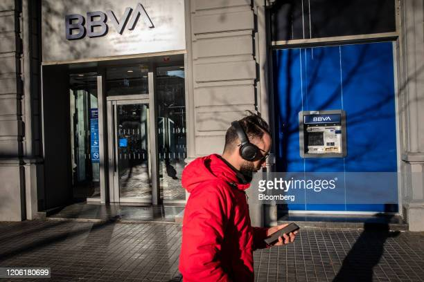 A pedestrian wearing headphones checks his smartphone as he passes by a Banco Bilbao Vizcaya Argentaria SA bank branch in Barcelona Spain on Saturday...