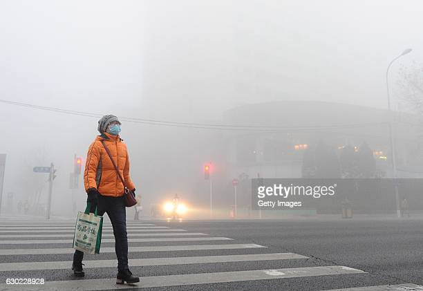A pedestrian wearing mask walks along a street in heavy smog on December 19 2016 in Dalian China At least 24 cities in North China issued red alerts...