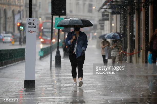 Pedestrian wearing PPE , of a face mask or covering as a precautionary measure against COVID-19, shelters under an umbrella they are caught in a...