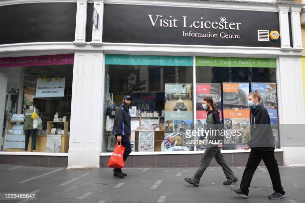 Pedestrian wearing PPE of a face mask or covering as a precautionary measure against spreading COVID19 walk past the closed information Centre in the...