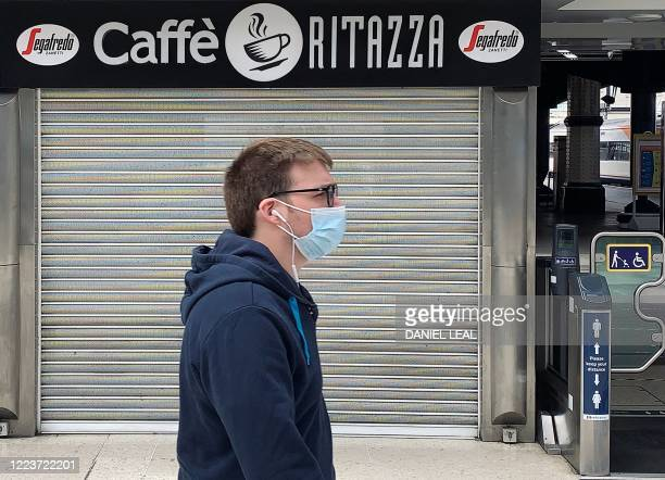Pedestrian wearing PPE , of a face mask or covering as a precautionary measure against spreading COVID-19, walks past a closed-down and shuttered...