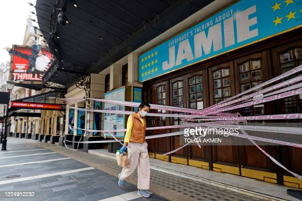 Pedestrian wearing PPE , of a face mask or covering as a precautionary measure against spreading COVID-19, walks past the Lyric and Apollo Theatres,...
