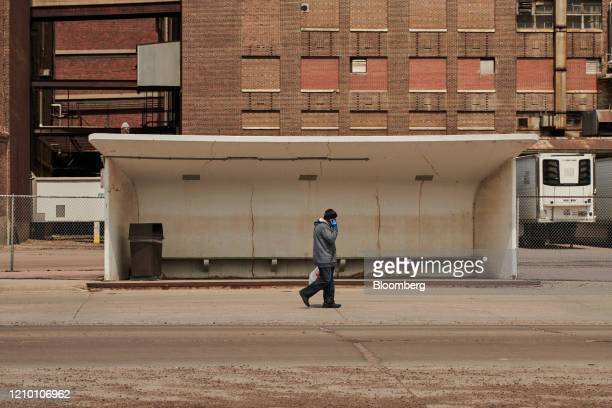 A pedestrian wearing protective gloves passes in front of an empty bus stop outside the closed Smithfield Foods Inc plant in Sioux Falls South Dakota...