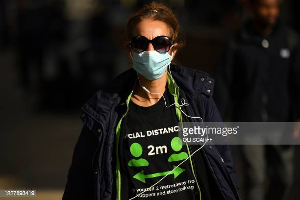 A pedestrian wearing tshirt promoting social distancing and a face mask or covering due to the COVID19 pandemic walks along the street in Manchester...