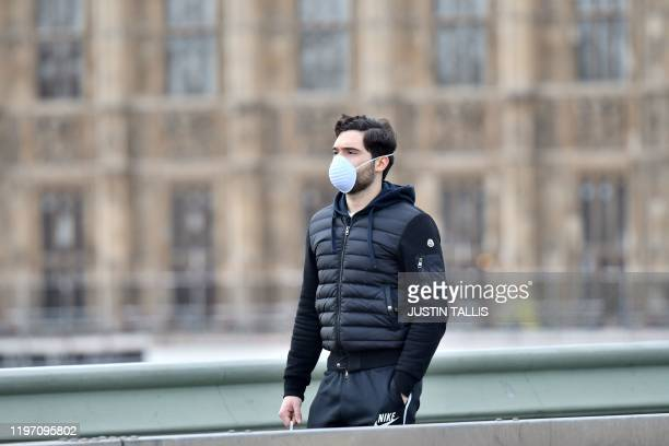 A pedestrian wears a face mask as he walks along the Thames embankment in central London on January 28 2020 Around 1500 people who came to Britain...