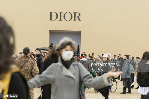 A pedestrian wears a face mask as visitors gather outside a popup building for the Christian Dior SE catwalk show during Paris Fashion Week at...