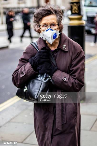 Pedestrian wears a face mask outside The National Portrait Gallery during London Fashion Week on February 17, 2020 in London, UK.
