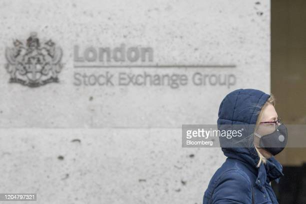 A pedestrian wears a protective face mask as she walks past the London Stock Exchange in London UK on Monday Mar 2 2020 From stocking up on dried and...