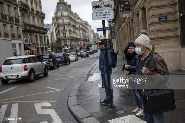 A pedestrian wears a protective face mask while waiting to cross a road in Paris France on Tuesday March 10 2020 The euroarea economy may be headed...