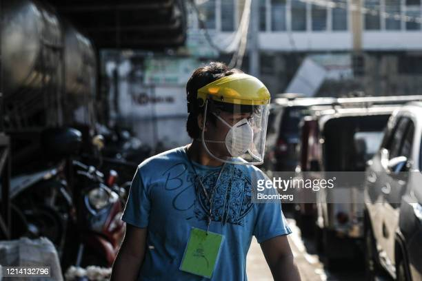 Pedestrian wears a protective mask and a face shield at a market during a partial lockdown imposed due to the coronavirus in Quezon City, Metro...