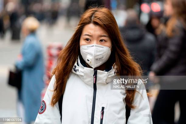Pedestrian wears a surgical mask while walking along London's Oxford Street in central London on January 25, 2020. - European airports from London to...
