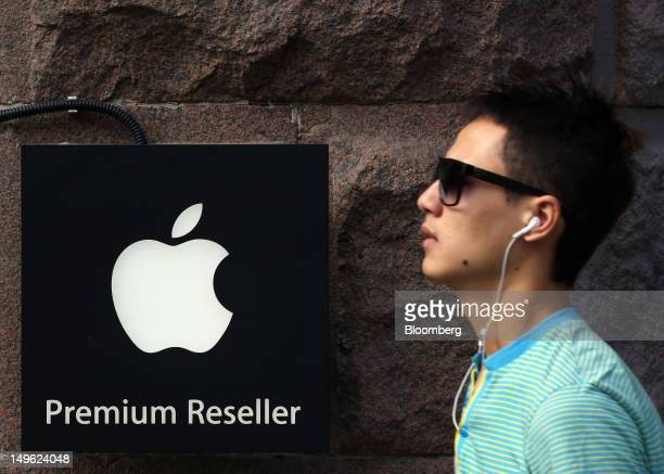 A pedestrian wears Apple Inc headphones as he passes an Apple company logo outside a reStore a premium Apple product reseller in Moscow Russia on...