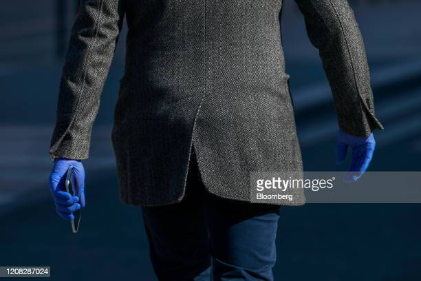 Pedestrian wears disposable gloves as he carries his mobile phone in Stockholm, Sweden, on Thursday, March 26, 2020. Sweden is starting to look like...
