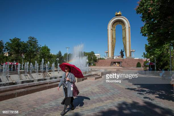 A pedestrian with a red umbrella walks through a park near the statue of Ismoili Somoni in Dushanbe Tajikistan on Saturday April 21 2018 Flung into...