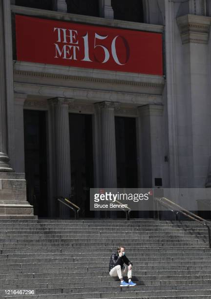 A pedestrian with a surgical mask sits on the steps at The Metropolitan Museum of Art on April 02 2020 in New York City Currently over 92000 people...