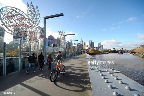 Pedestrians and a cyclist cross the Sandridge Bridge that spans the Yarra River in central Melbourne Australia on Sunday June 2 2013 The Australian...