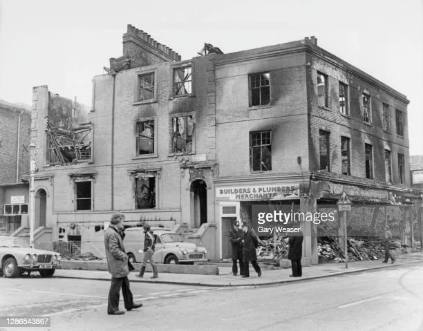 Pedestrians and a group of police officers stand before a fire-damaged building on Chaucer Road after a night of rioting on the streets of Brixton,...