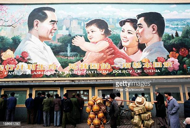 Pedestrians and a man carrying baskets pass by a huge billboard extolling the virtues of China's 'One Child Family' policy