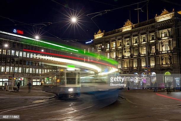 Pedestrians and a tram pass UBS Group AG left and Credit Suisse Group AG's headquarters on Paradeplatz in Zurich Switzerland on Tuesday Feb 10 2015...