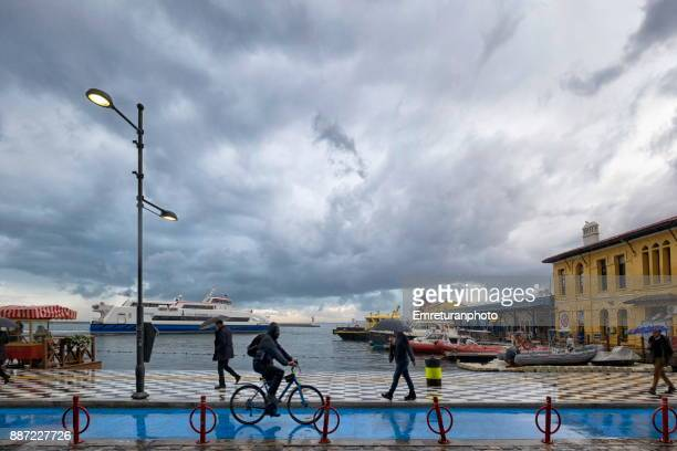 pedestrians and biker going to work at waterfront in izmir on a rainy winter day. - emreturanphoto foto e immagini stock