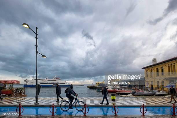 pedestrians and biker going to work at waterfront in izmir on a rainy winter day. - emreturanphoto stockfoto's en -beelden