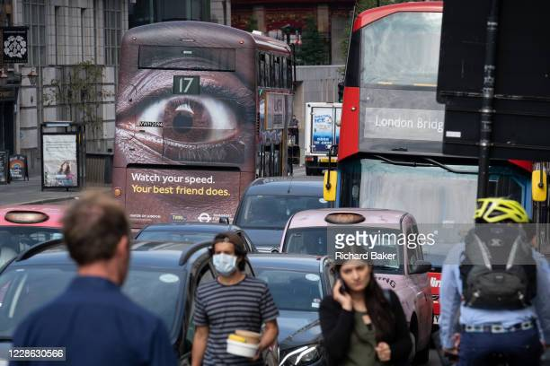 Pedestrians and busy traffic on the Farringdon Road in the City of London with a London bus carrying an ad about speeding in the capital, on 16th...