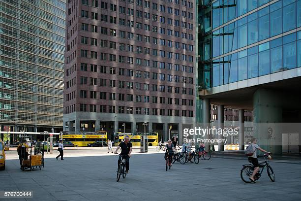 pedestrians and bycicle riders by the sony centre's tower, deutsche bahn's corporate headquarters at potsdamer platz in berlin, germany - limestone pavement stock pictures, royalty-free photos & images