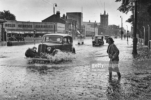 Pedestrians and cars pass long flooded roads, circa 1940.