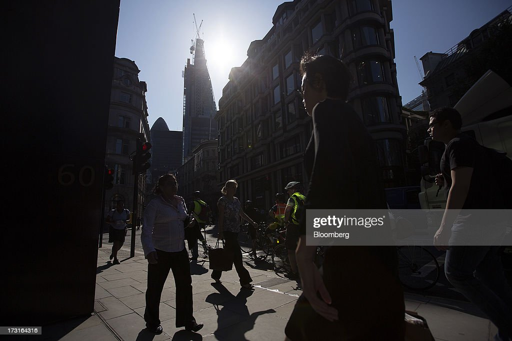 Pedestrians and commuters walk across a footpath in central London, U.K., on Monday, July 8, 2013. Britain's economy could be in line for a period of 'strong catch-up growth' once it gets through the current weakness, according to Capital Economics Ltd. Photographer: Simon Dawson/Bloomberg via Getty Images