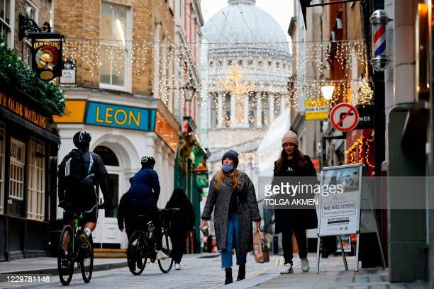 Pedestrians and cyclists make their way through the streets of the City of London in London on November 25, 2020. - Britain's economy is set to...