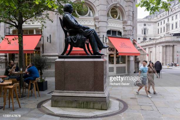 Pedestrians and lunchtime drinkers alongside the statue of Victorian philanthropist, entrepreneur and banker George Peabody , in the City of London,...