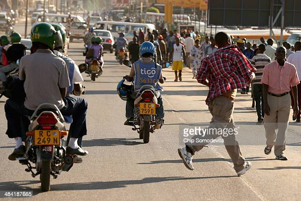 Pedestrians and motorcycle taxis called 'bodaboda' in East Africa mix in the street near the Nyabugogo neighborhood bus park April 9 2014 in Kigali...