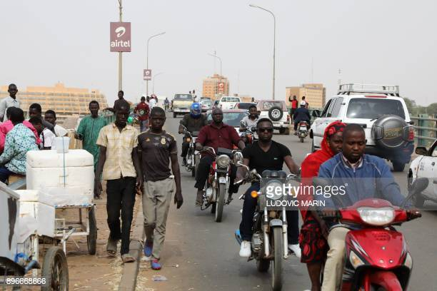 Pedestrians and motorists cross a bridge over the Niger River on December 21 in Niamey / AFP PHOTO / LUDOVIC MARIN