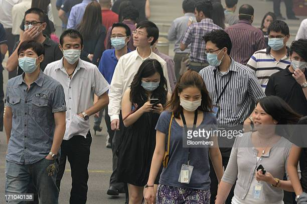 Pedestrians and office workers wear face masks as they cross a street in Singapore, on Friday, June 21, 2013. Singapore's smog hit its worst level,...