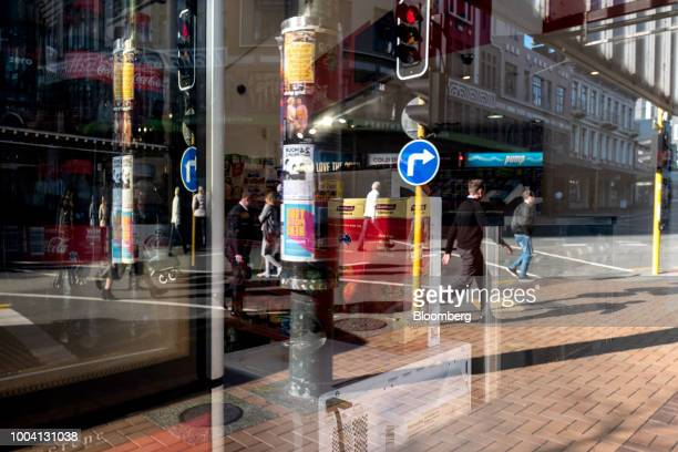 Pedestrians and road signs are reflected on a window of a store in the central business district of Wellington New Zealand on Wednesday July 18 2018...
