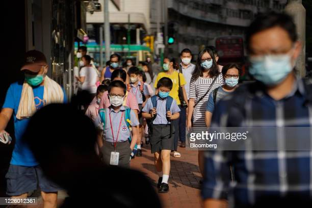 Pedestrians and schoolchildren wearing protective masks walk along a sidewalk in Hong Kong China on Friday July 10 2020 Hong Kong is closing its...