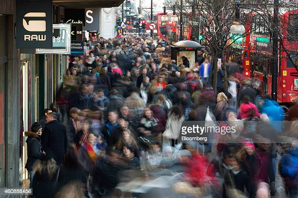 Pedestrians and shoppers are seen in this long exposure photograph as they walk past stores and red London buses on Oxford Street in London UK on...