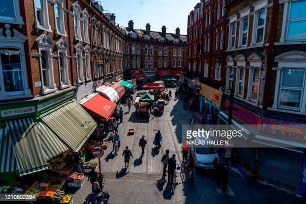 Pedestrians and shoppers are seen walking by market stalls on Electric Avenue in Brixton south London on April 23 2020 as life in Britain continues...