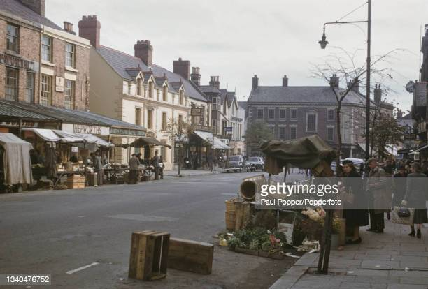 Pedestrians and shoppers buy produce from market stalls lining a main street in the centre of the town of Mold in Flintshire, Wales circa 1960.