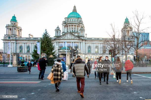 Pedestrians and shoppers cross a road beside Belfast City Hall in Belfast city centre on Christmas Eve, December 24, 2020 as the Province prepares to...