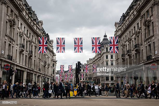 Pedestrians and shoppers cross a road junction at Oxford Circus as British Union flags hang suspended above Regent Street in London UK on Tuesday May...