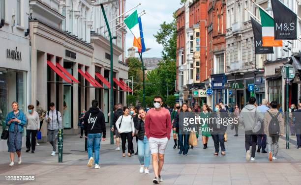 Pedestrians and shoppers, some wearing a face mask or covering due to the COVID-19 pandemic, walks past shops in Dublin on September 18 amid reports...